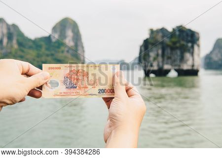 Someone Hands Showing 200,000 Dong Of Vietnamese Banknotes With An Iconic Karst In Halong Bay, Unesc