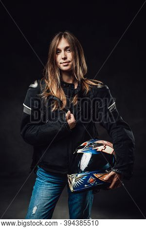 Female Motorcyclist Dressed In Black Jacket With Jeans Poses In Dark Background Holding Protective H