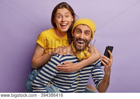 Photo Of Young Boyfriend And Girlfriend Have Fun Together, Man Gives Piggyback Ride To Female, Use M