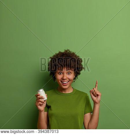 Happy Dark Skinned Girl Leads Healthy Lifestyle, Keeps Fit, Holds Jar Of Orgnaic Yoghurt For Breakfa