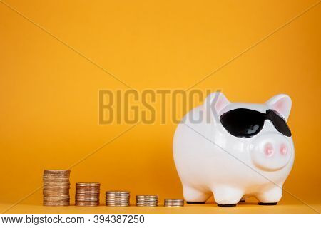 Financial Savings For A Good Life. Piggy Bank And Coins Yellow Background