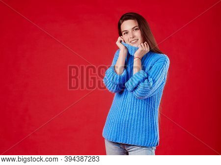 Beautiful Girl In A Warm Sweater On A Red Background.