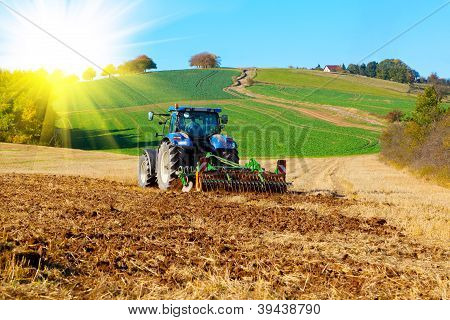 Tractor plows a field in the spring with sunlight poster