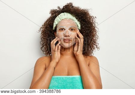 Serious Dark Skinned Woman Wears Natural Sheet Mask, Cares About Facial Skin, Has Bushy Crisp Hair,