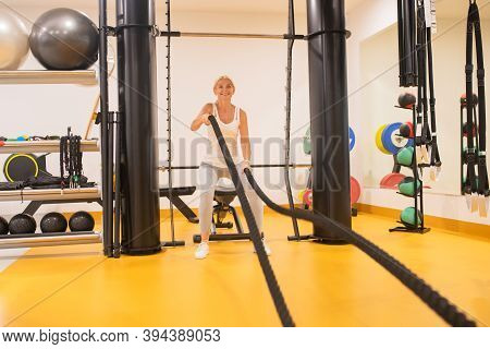 Blonde Woman In Sportswear Pulling The Ropes In Gym