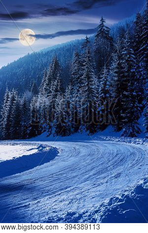 Snow Covered Road Through Forest In Mountains At Night. Beautiful Winter Scenery In Full Moon Light.