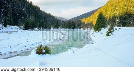 Mountain River In Winter. Spruce Forest On Snow Covered Shore. Cold Sunny Morning Weather With Cloud