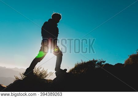 Silhouettes Of Young Boy Hiking At Sunset Mountains