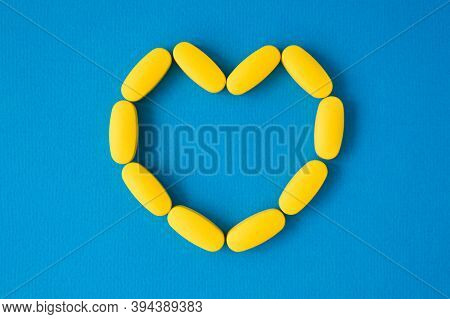 Health Protect Concept Of Yellow Pills Tablets In Heart Shape On Blue Surface