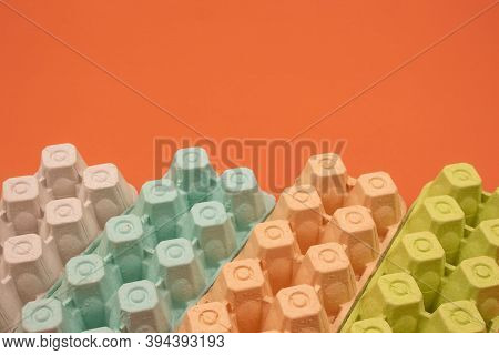 Multicolored Organic Egg Trays On Orange Background With Copyspace For Your Text. Biodegradable And