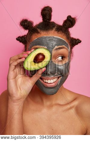 Photo Of Happy Woman Has Healthy Glow Skin, Applies Clay Mask On Face, Covers Eye With Piece Of Avoc