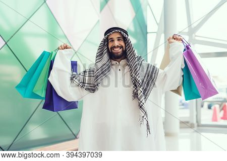 Young Arabian Man With Packages Standing In Mall.