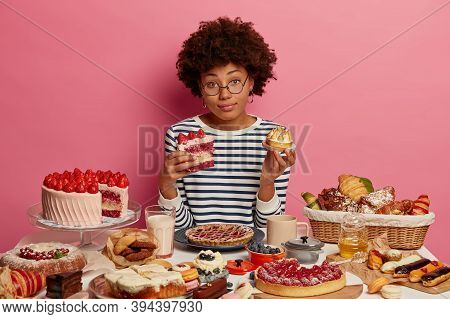 Confused Dark Skinned Woman Holds Piece Of Cake And Muffin, Hesitates What To Eat First, Being Real