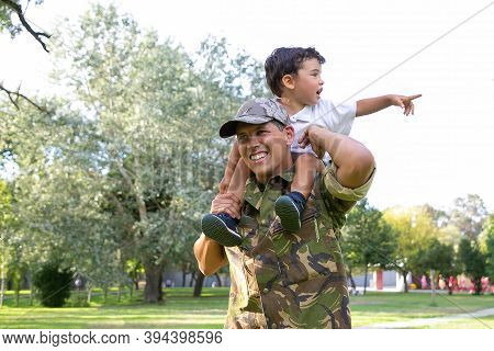 Exited Little Boy Sitting On Dad Neck And Pointing Away. Caucasian Father Holding Son Legs, Smiling,