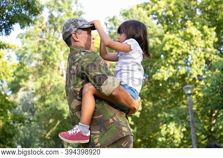 Serious Dad In Military Uniform Holding Daughter On Hands, Looking At Her And Standing Outdoors. Con