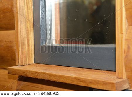 A Wooden Window Sill With A Upvc Plastic Window Installed In A House With Log Siding Panels Facade.
