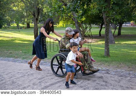 Happy Mom, Kids And Disabled Dad In Military Uniform Walking In Park. Pretty Mother Pushing Wheelcha
