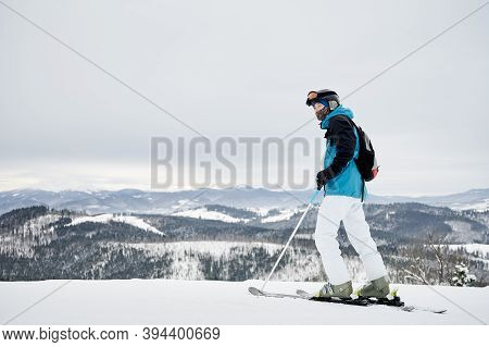 Full Length Man Skier Looking At Beautiful Snowy Mountains. Young Man Wearing Ski Suit, Backpack, Pr