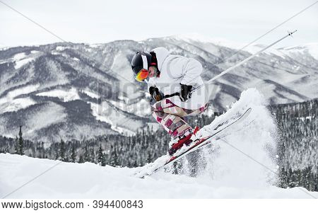 Full Length Of Male Skier In Jacket And Helmet Skiing On Fresh Powder Snow With Beautiful Winter Mou
