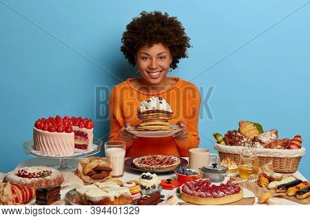 Indoor Shot Of Curly Woman Has Sweet Bakery Lunchtime, Holds Plate With Delicious Sugary Creamy Panc
