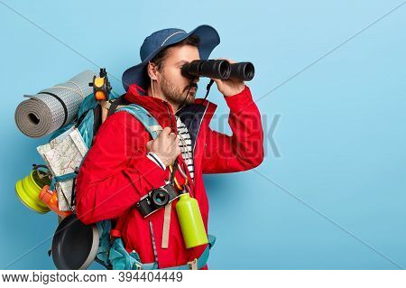 Trekking, Camping, Hiking Concept. Photo Of Serious Male Tourist Uses Binoculars To Observe Surround