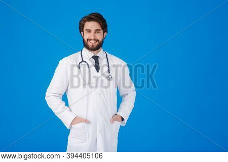 Young Bearded Doctor On A Blue Background. Emotions Of Joy And A Smile At The Doctor Looking At The
