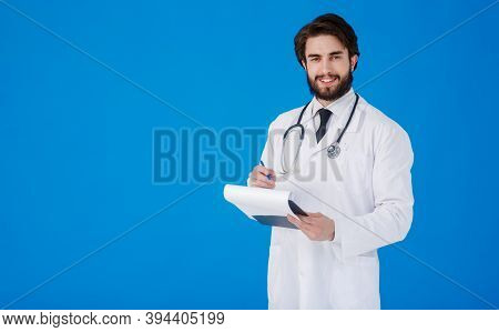 Young Bearded Doctor. In A White Medical Coat On A Blue Background Writes Down The Patients Complain