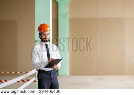 A Young Bearded Architect In A Construction Helmet On A Construction Site Checks The Result.