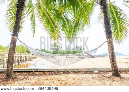 Hammock Between Two Coconut Trees On A Tropical Island With Beautiful Beach