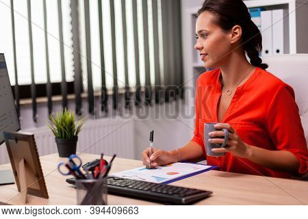 Executive Businesswoman Entrepreneur Writing Financial Sales Report Looking At Screen Wearing Red. S