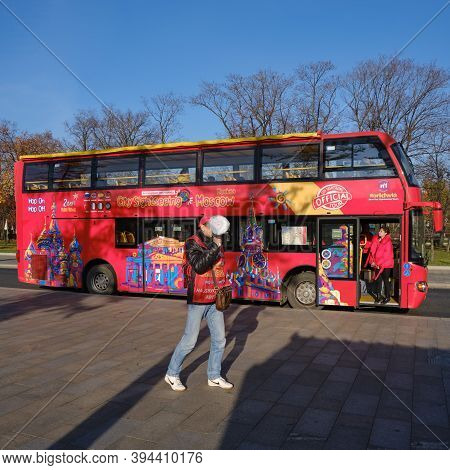 Red Tour Bus For Excursions On Moscow Street. Touting Tourists With A Megaphone For A Trip Around Th