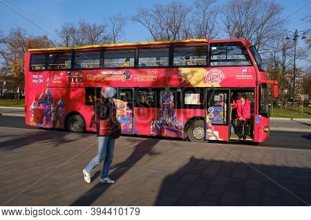The Red Sightseeing Bus For Tourists On The Streets Of Moscow. Barker On A Tour With A Megaphone For