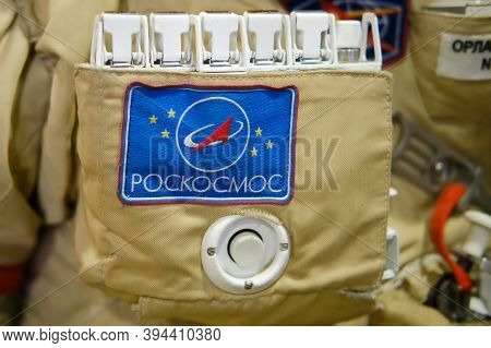 The Emblem Of Roscosmos On The Suit Of The Astronaut With The Iss. Roscosmos Inscription - Text On A