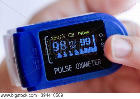Pulse Oximeter Display Closeup On Finger. Covid-19, Healthcare Concept. Pulse Rate Health Tester Oxi