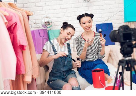 Two Fashion Blogger Girls Hold Up Brushes And Mascara To Camera.
