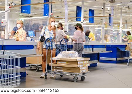 People In Medical Masks At The Checkout Of The Ikea Store. Women Stand With Purchases In A Furniture