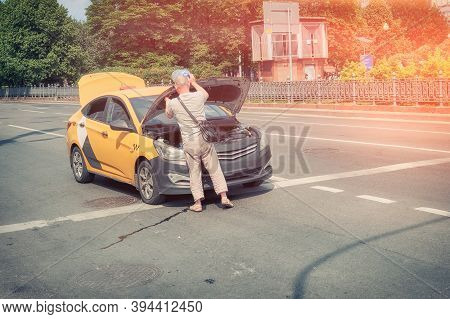 Taxi Driver Saves The Car From Overheating On A Hot Summer Day. Problems With Engine In Car Standing