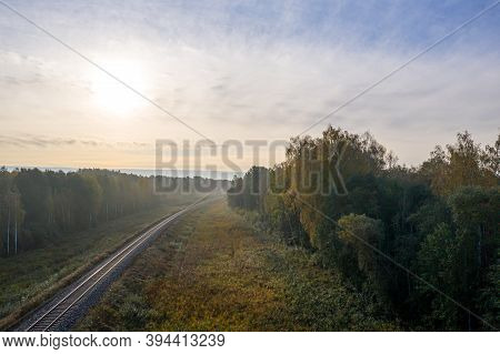 Aerial View Of Railroad In Forest At Foggy Autumn Morning, Top View Of Rural Railroad In Fall