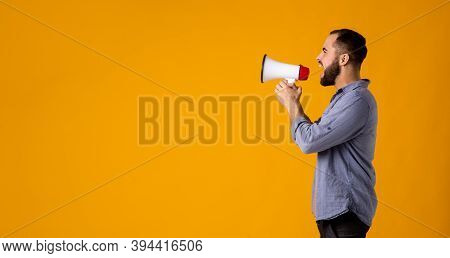 A Bearded Man In A Casual Shirt With A Loudspeaker In His Hands Shouts Into A Megaphone On A Yellow