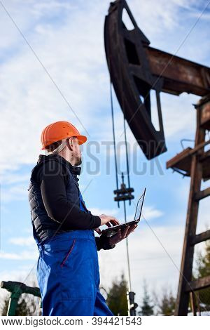 Oil Man Holding Notebook And Looking At Oil Pump Rocker-machine. Male Worker In Uniform And Helmet U