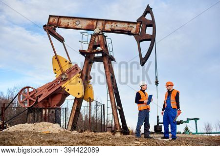 Two Petroleum Engineers In Helmets And Work Vests Standing On Territory Of Oil Field With Oil Well P