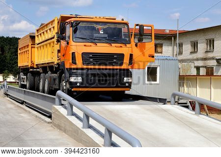 Orange Truck With Grain Is Weighed On The Scales In The Grain Storage Area. Truck Scales