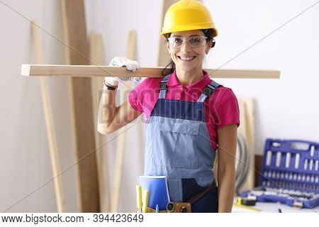 Woman Carpenter In Protective Helmet And Glasses Holding Wooden Board On Shoulder. Carpenter Profess