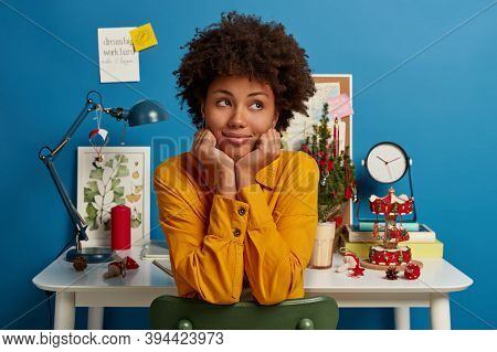 Thoughtful Contemplative Afro American Woman Sits On Chair, Holds Chin, Looks Thoughtfully Aside, St
