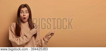 Shocked Dark Haired Woman Points Aside On Blank Space, Has Wide Opened Mouth, Demonstrates Shocking