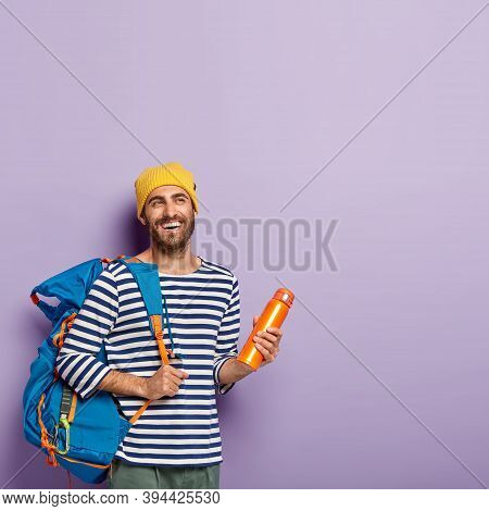 Vertical Shot Of Happy Unshaven Male Backpacker Carries Big Tourist Rucksack, Holds Flask, Enjoys Tr