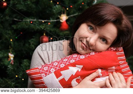 Happy Young Beautiful Smiling Woman Posing Near Christmas Tree Hugs Red Pillow With Christmas Tree A