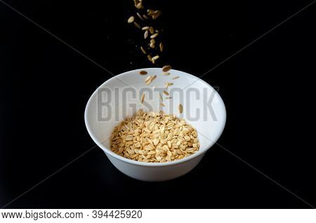 Oat Flakes Flying Out Of Wooden Bowl Isolated On White And Black Background, Falling Oats