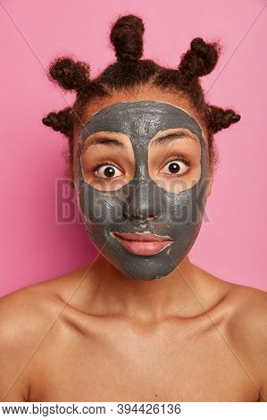 Close Up Portrait Of Naked Woman Looks With Wonder At Camera, Stands Naked, Applies Clay Mask To Rem