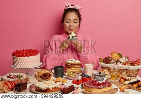 Photo Of Adorable Korean Woman Holds Yummy Sugary Dessert Or Muffin, Isolated Over Pink Background,